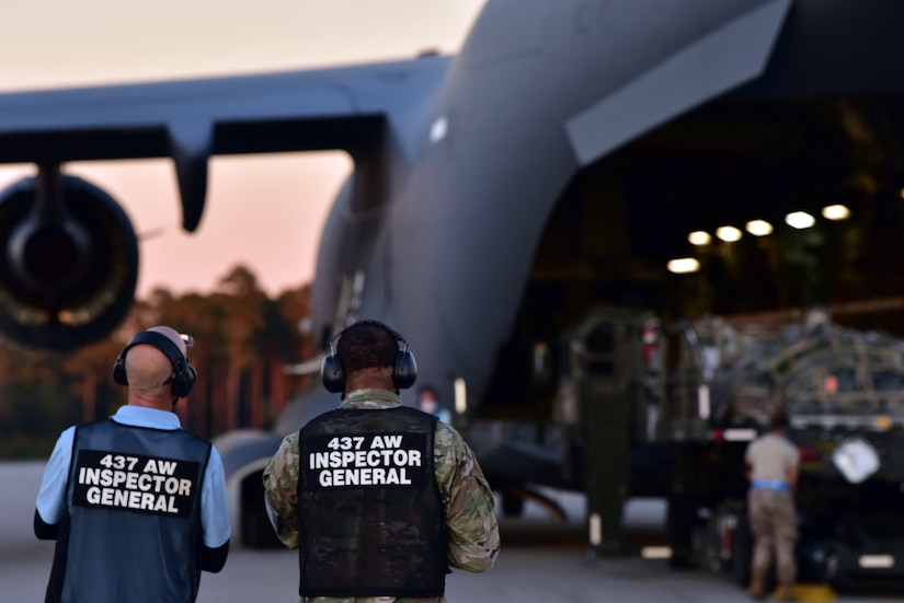 U.S. Air Force Master Sgt. Bradley Moorer, an Inspector General Wing Inspection Team superintendent for the 437th Airlift Wing (left), and Mark Vickers, the 437th AW IG director of inspections (right), watch as a C-17 Globemaster III containing Airmen and supplies lands, at McEntire Joint National Guard Base, S.C., Nov. 16, 2020. Palmetto Challenge is a global mobilization exercise held at McEntire Joint National Guard Base, S.C. The exercise is held in order to develop readiness and awareness in a simulated deployed environment for over 100 Airmen from Joint Base Charleston.