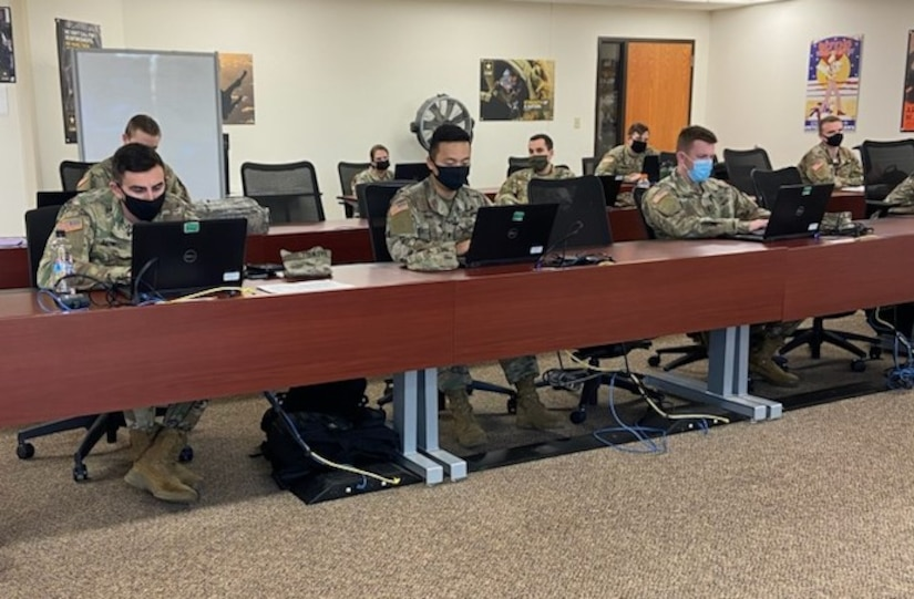 soldiers in uniform sitting at computer terminals