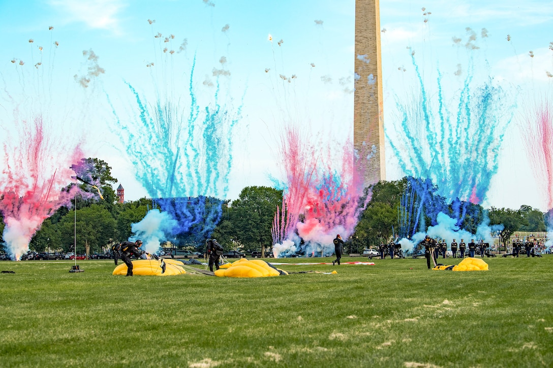 Blue and pink fireworks erupt as soldiers gather their parachutes on grounds in front of the Washington Monument.