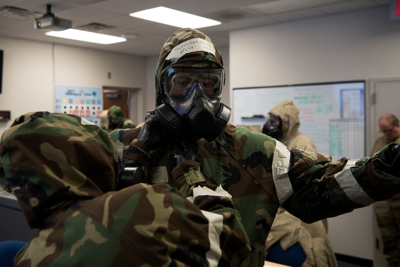 U.S. Air Force Master Sgt. Ian Ouellette, the superintendent for the 628th Air Base Wing Inspector General office, grades Airmen from the Emergency Operations Center (EOC) on how efficiently they equip Mission Oriented Protective Posture gear (MOPP), at McEntire Joint National Guard Base, S.C., Nov. 16, 2020. Palmetto Challenge is a global mobilization exercise held at McEntire Joint National Guard Base, S.C., and Pope Army Airfield, N.C. The exercise is held in order to develop readiness and awareness in a simulated deployed environment for over 100 Airmen from Joint Base Charleston.