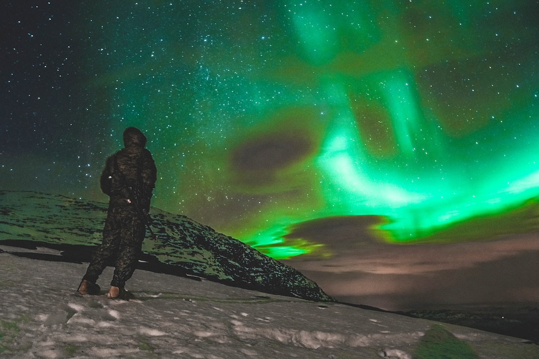 A Marine stands in snow and looks toward the night sky, illuminated in green by the Northern Lights.