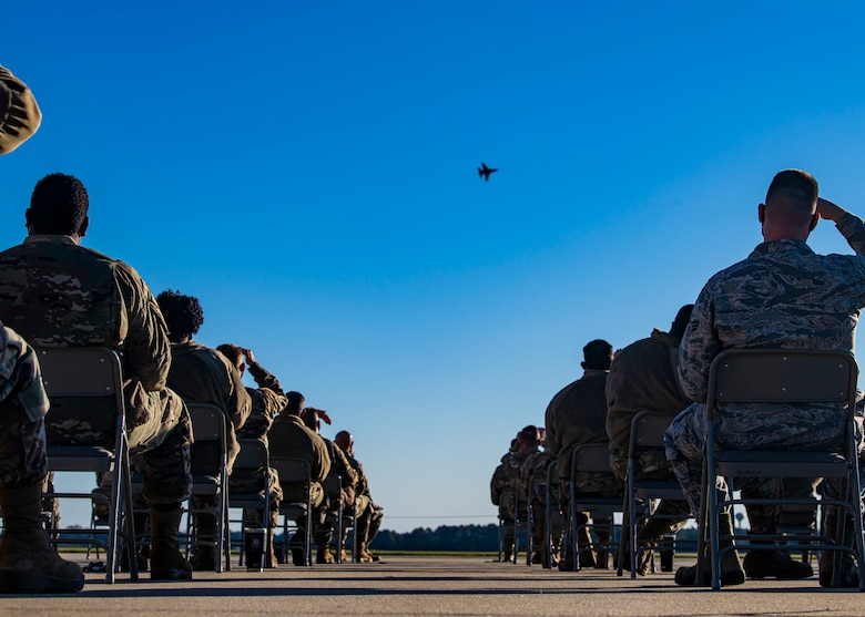 A photo of a group of Airmen watch a demonstration on the flightline.