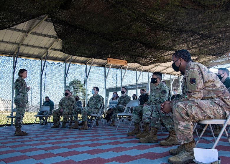 A photo of Airmen listening to a speaker.