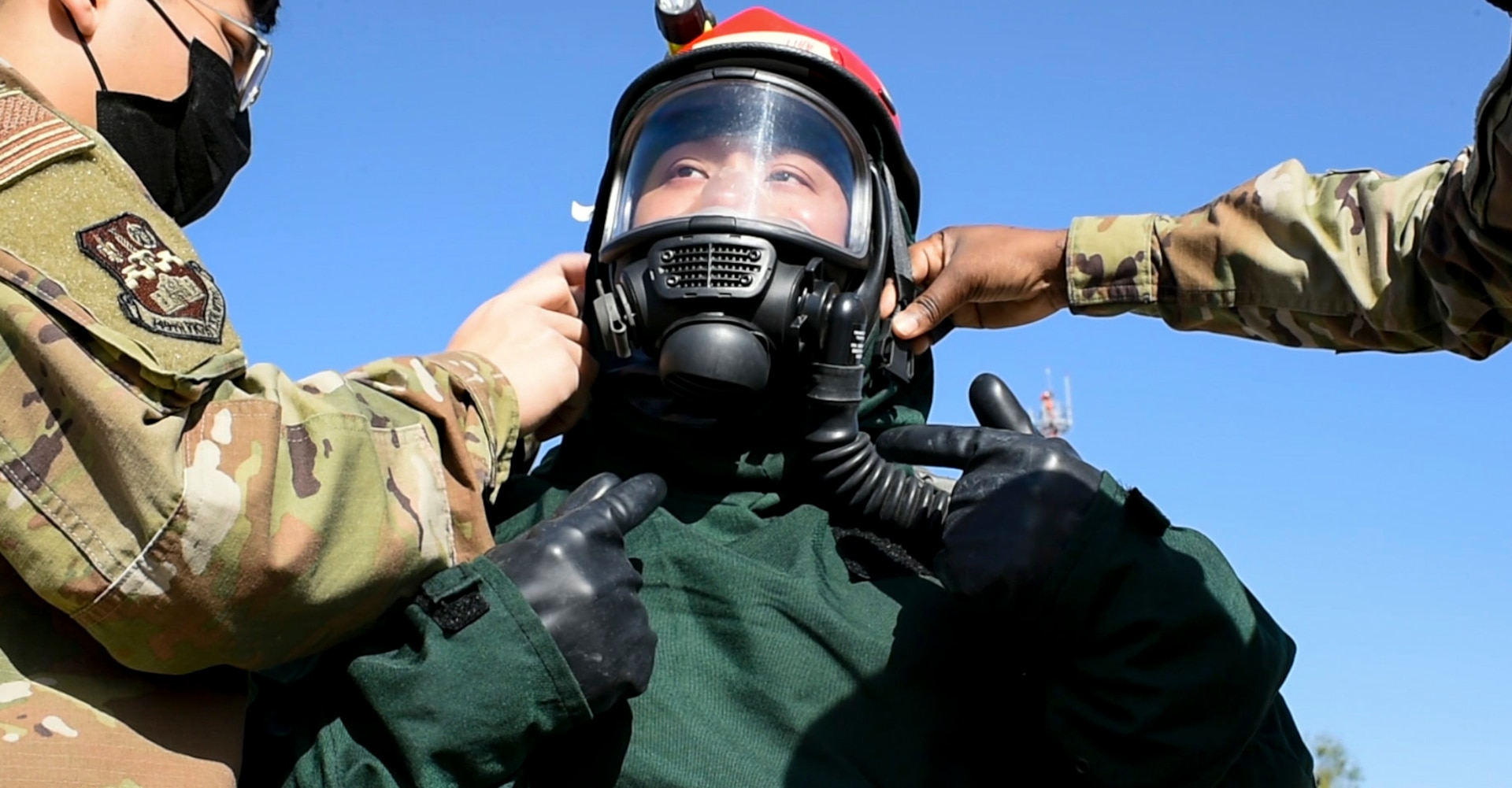 Staff Sgt. Benjamin Le (center) is assisted by Airman 1st Class Tyler Jimison (left) and Airman 1st Class Beatrice Hiyunsaba (right), in getting his helmet properly fastened Nov. 15 at Joint Base San Antonio-Lackland. All are assigned to the 149th Fighter Wing fatality search and recovery team, or FSRT, and were training on how to move into a contaminated area and recover remains after a chemical disaster.
