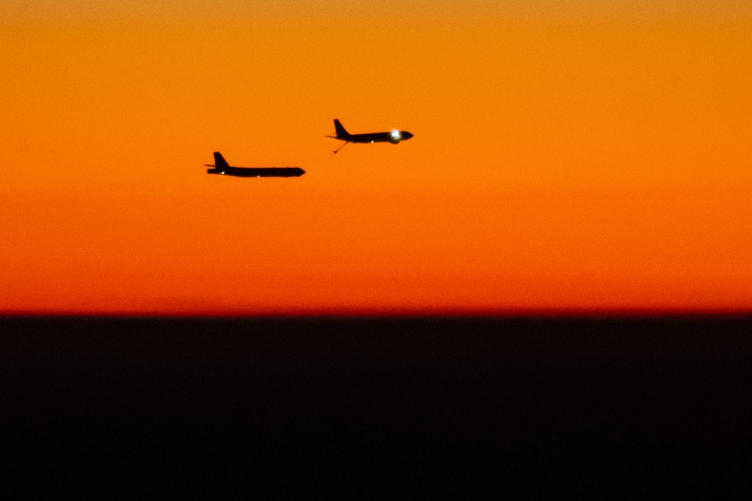 Two aircraft fly next to each other.