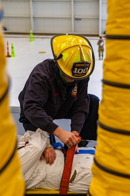 Adam Zelenko, Allegheny County Fire Rescue firefighter straps in Staff Sgt. Cory Burtom 911th Maintenance Squadron aircraft hydraulic systems maintainer in a stretcher at the Pittsburgh International Airport Air Reserve Station, Pennsylvania, Nov. 3, 2020.