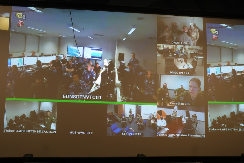 Photo of video screen with multiple locations of U.S. and Coalition forces sitting at tables.