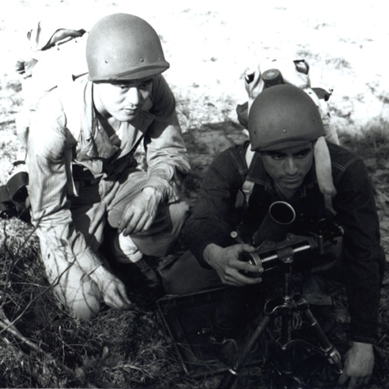 Two men set up a mortar launcher on the ground.