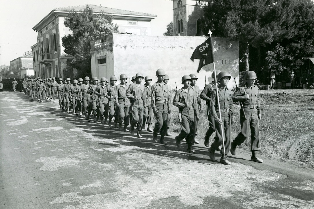 Several men in lines of two march down a street.