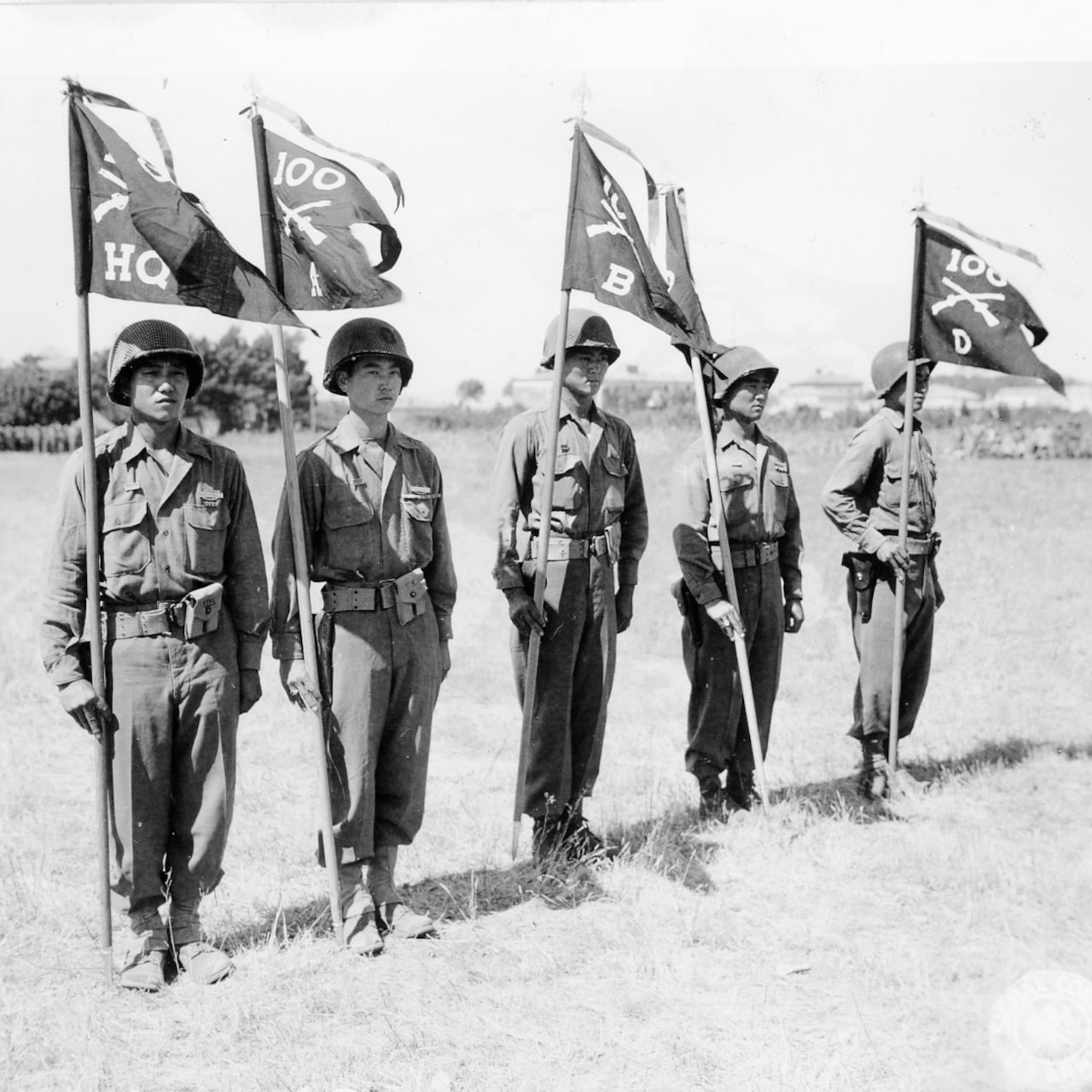 Five men stand at attention while holding flags.