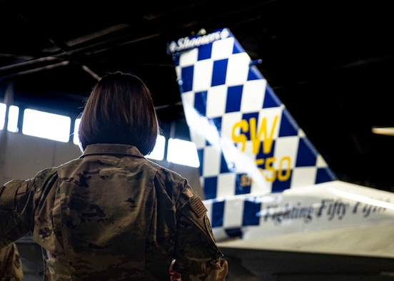 A photo of an Airman standing with a tail flash.