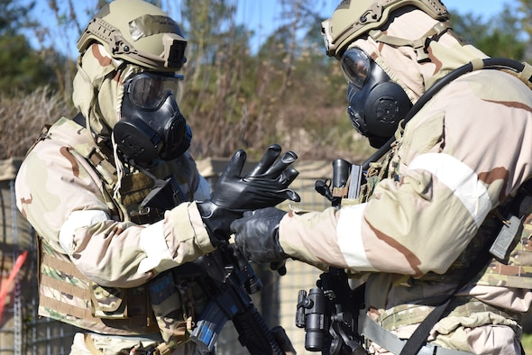 Photo shows two Airmen putting on chem gear with green smoke behind them.
