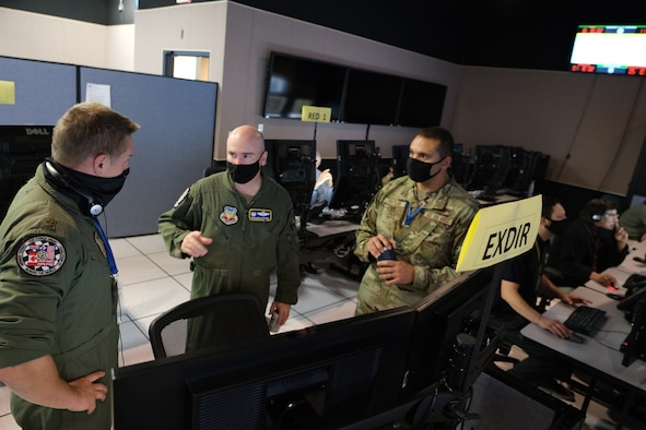Three U.S. Air Force officers stand in front of computer screens.