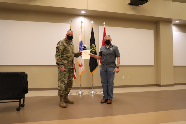 U.S. Army Civil Affairs and Psychological Operations Command (Airborne) Commanding General, Brig. Gen. Jeffrey C. Coggin, presents the Federal Length of Service Award to Billy L. Wells for 10 years of federal service during the Soldier and Department of the Army Civilian recognition award ceremony at USACAPOC(A) Headquarters on Fort Bragg, N.C., Nov. 17, 2020. The recognition award ceremony was held to recognize 12 USACAPOC(A) Soldiers and DA civilians for Federal Length of Service Awards, Honorary Awards, Retirement recognition, and military awards.