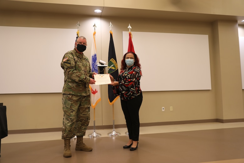 U.S. Army Civil Affairs and Psychological Operations Command (Airborne) Commanding General, Brig. Gen. Jeffrey C. Coggin, presents the Commanders Award for Civilian Service to Elizabeth Fernandez-Javier during the Soldier and Department of the Army Civilian recognition award ceremony at USACAPOC(A) Headquarters, Fort Bragg, N.C., Nov. 17, 2020. The recognition award ceremony was held to recognize 12 USACAPOC(A) Soldiers and DA civilians for Federal Length of Service Awards, Honorary Awards, Retirement recognition, and military awards.