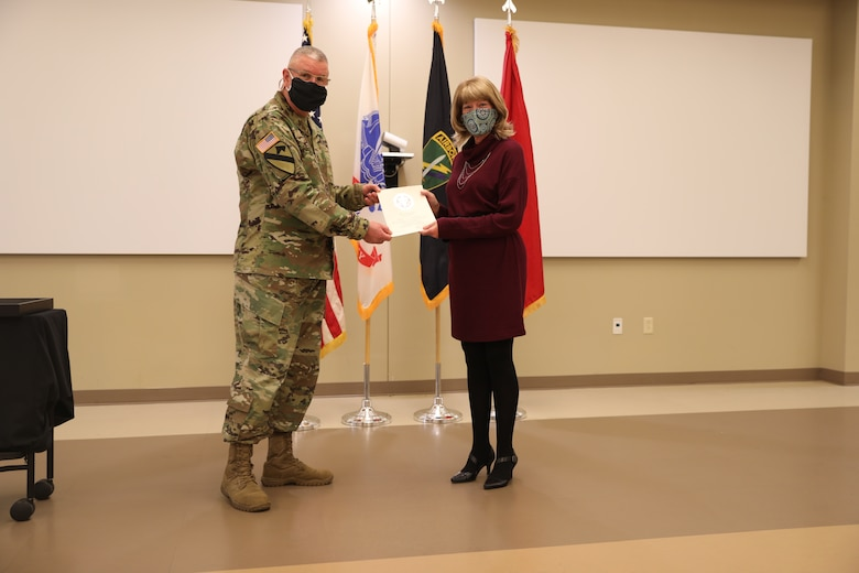 U.S. Army Civil Affairs and Psychological Operations Command (Airborne) Commanding General, Brig. Gen. Jeffrey C. Coggin, presents the Federal Length of Service Award to Kathy L. Futrell for 25 years of federal service during the Soldier and Department of the Army Civilian recognition award ceremony at USACAPOC(A) Headquarters, Fort Bragg, N.C., Nov. 17, 2020. The recognition award ceremony was held to recognize 12 USACAPOC(A) Soldiers and DA civilians for Federal Length of Service Awards, Honorary Awards, Retirement recognition, and military awards.