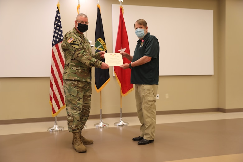 U.S. Army Civil Affairs and Psychological Operations Command (Airborne) Commanding General, Brig. Gen. Jeffrey C. Coggin, presents the Superior Civilian Service Award to Robert E. Spears for service as the Training Specialist for USACAPOC(A) for over 28 years, and recognizes his impending retirement from federal service, presenting a Department of the Army Certificate of Appreciation, during the Soldier and Department of the Army Civilian recognition award ceremony at USACAPOC(A) Headquarters, Fort Bragg, N.C., Nov. 17, 2020. The recognition award ceremony was held to recognize 12 USACAPOC(A) Soldiers and DA civilians for Federal Length of Service Awards, Honorary Awards, Retirement recognition, and military awards.
