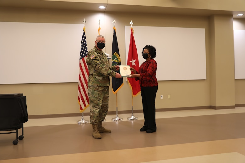 U.S. Army Civil Affairs and Psychological Operations Command (Airborne) Commanding General, Brig. Gen. Jeffrey C. Coggin, presents the Federal Length of Service Award to Angela T. Hammond for 35 years of federal service during the Soldier and Department of the Army Civilian recognition award ceremony at USACAPOC(A) Headquarters, Fort Bragg, N.C., Nov. 17, 2020. The recognition award ceremony was held to recognize 12 USACAPOC(A) Soldiers and DA civilians for Federal Length of Service Awards, Honorary Awards, Retirement recognition, and military awards.