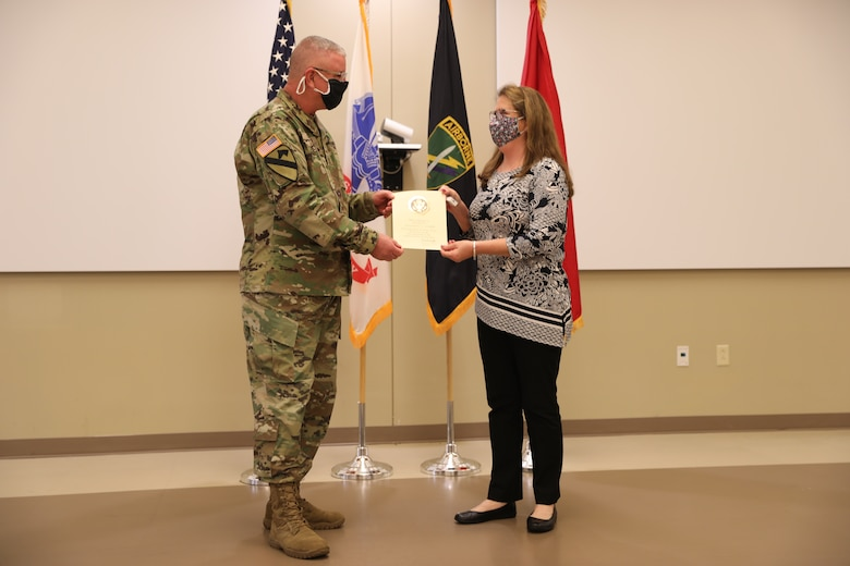 U.S. Army Civil Affairs and Psychological Operations Command (Airborne) Commanding General, Brig. Gen. Jeffrey C. Coggin, presents the Federal Length of Service Award to Elizabeth J. Holman for 40 years of federal service, and recognizes her impending retirement from federal service, presenting a Department of the Army Certificate of Appreciation, during the Soldier and Department of the Army Civilian recognition award ceremony at USACAPOC(A) Headquarters, Fort Bragg, N.C., Nov. 17, 2020. The recognition award ceremony was held to recognize 12 USACAPOC(A) Soldiers and DA civilians for Federal Length of Service Awards, Honorary Awards, Retirement recognition, and military awards.
