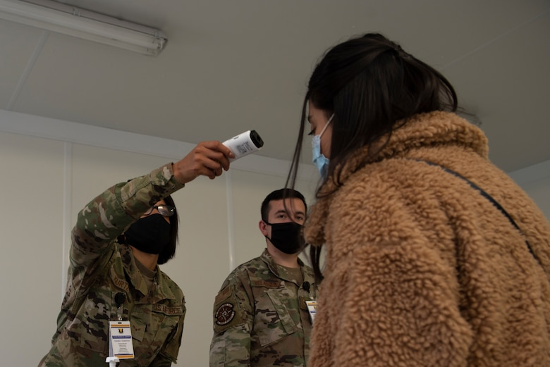 A photo of an Airman taking someone's temperature.