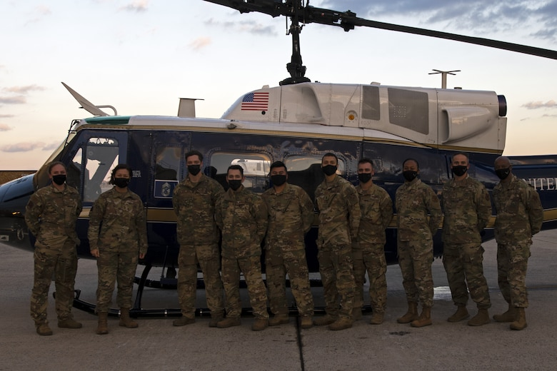 """The 316th Operations Group pose for a group photo with Chief Master Sgt. of the Air Force JoAnne Bass in front of a UH-1N """"Huey"""" at Joint Base Andrews, Md., Nov. 23, 2020. The UH-1N """"Huey"""" will eventually be phased out by the H-139A Grey Wolf. (U.S. Air Force Photo by Senior Airman Kaylea Berry)"""