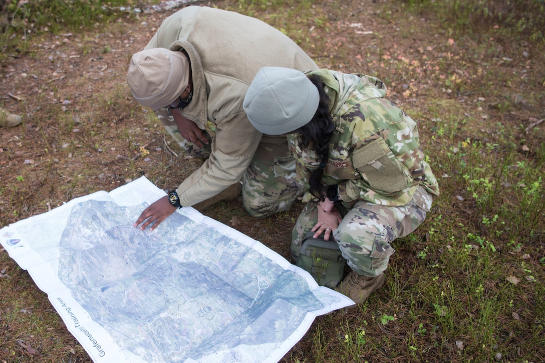 U.S. Airmen assigned to the 435th Contingency Response Group read a map while participating in a Survival, Evasion, Resistance and Escape navigation course during exercise Agile Wolf 21-01.