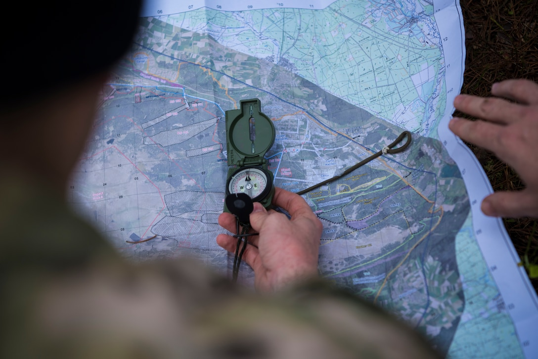 U.S. Air Force Staff Sgt. Ryan Silva, 435th Security Forces Squadron contingency response member, holds a compass against a map while participating in a Survival Evasion Resistance Escape navigation course during exercise Agile Wolf 21-01.