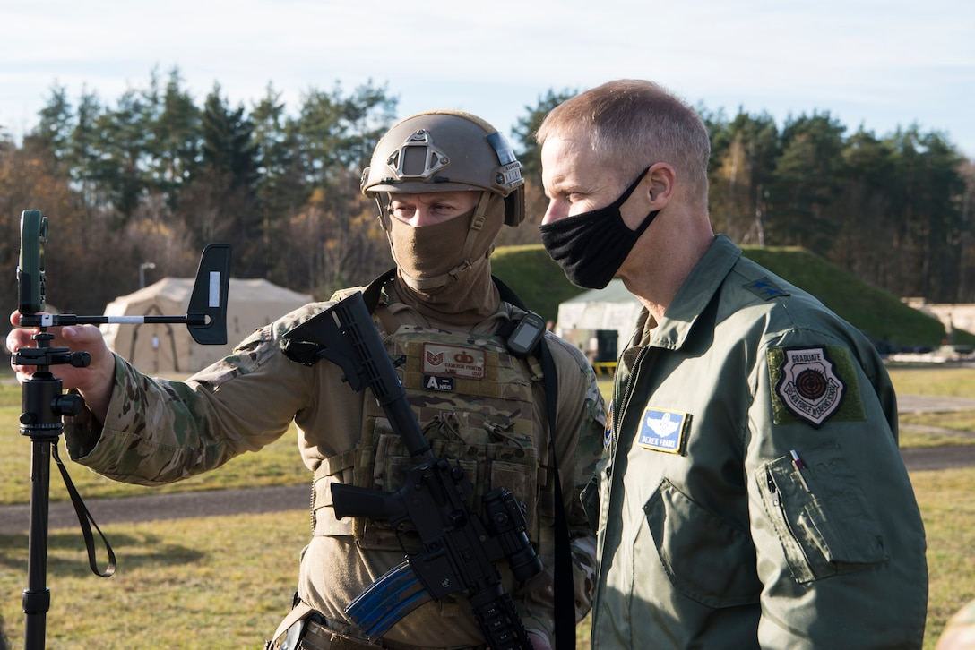 U.S. Air Force Tech. Sgt. Cameron Piontek, 435th Contingency Response Squadron contingency air traffic controller, left, shows Maj. Gen. Derek France, Headquarters U.S. Air Forces in Europe-Air Forces Africa strategic deterrence and nuclear integration operations director, a joint-terminal attack controller wind meter during exercise Agile Wolf 21-01.