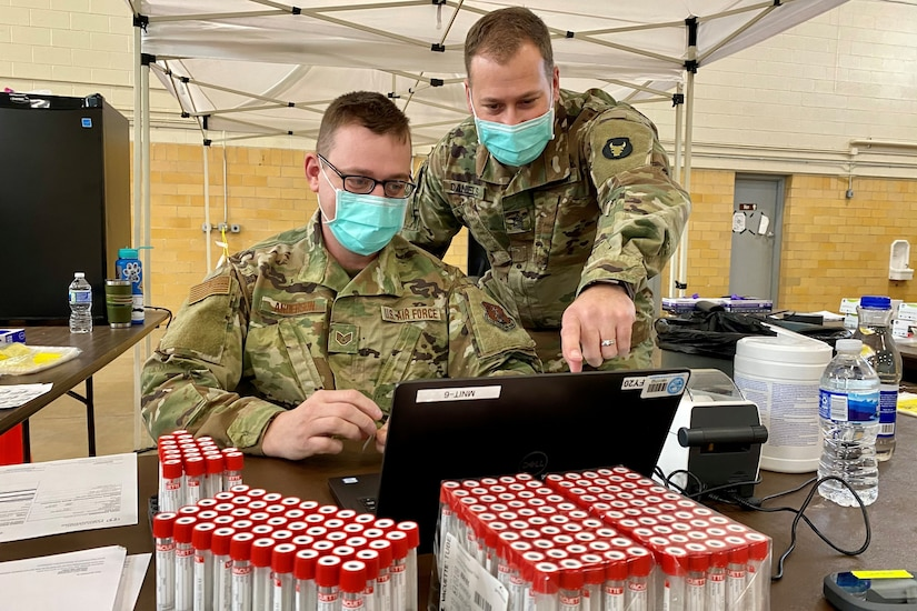 Two service members look at a computer monitor.
