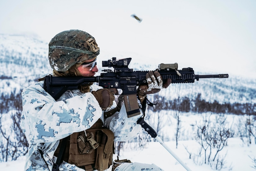 A Marine fires a weapon in a snowy forest.