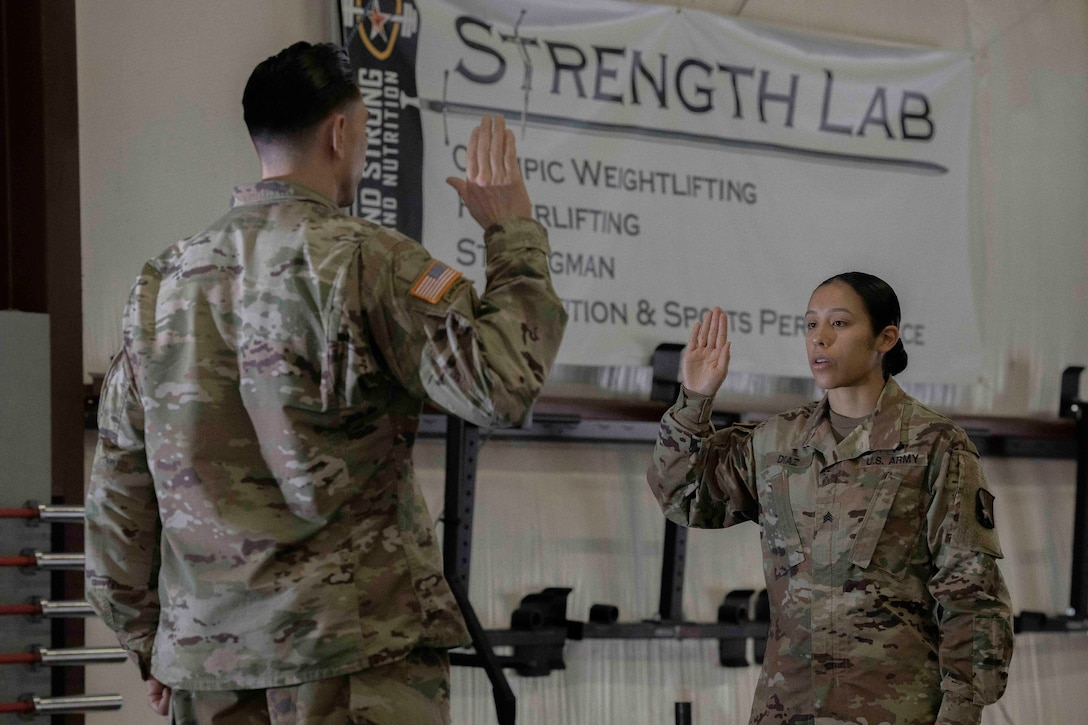 Two soldiers face each other with raised right hands.