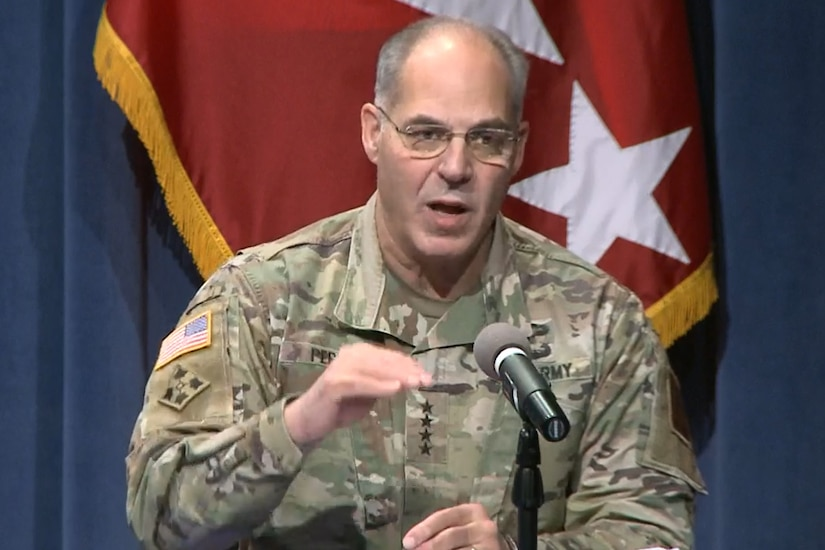 A man in a military uniform speaks into a microphone.