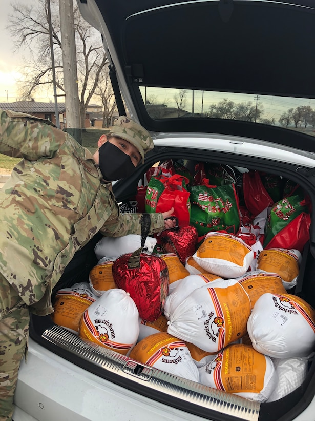Master Sgt. Erin Henning, 388th Maintenance Group first sergeant, poses next to a trunk full of Thanksgiving food items Nov. 20, 2020, at Hill Air Force Base, Utah. Operation Warm Heart, a first sergeant's program, teamed with the commissary to deliver bags filled with turkeys, hams and other goods items to assist Airmen and their families with the upcoming holiday. (Courtesy photo)