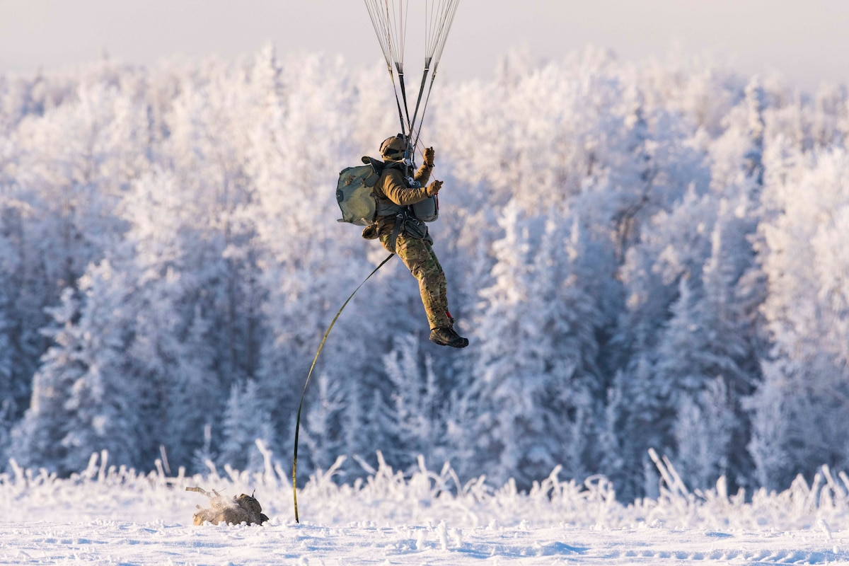 An airman descends from the sky with a parachute onto a snow-covered field with snow-covered trees in the background.