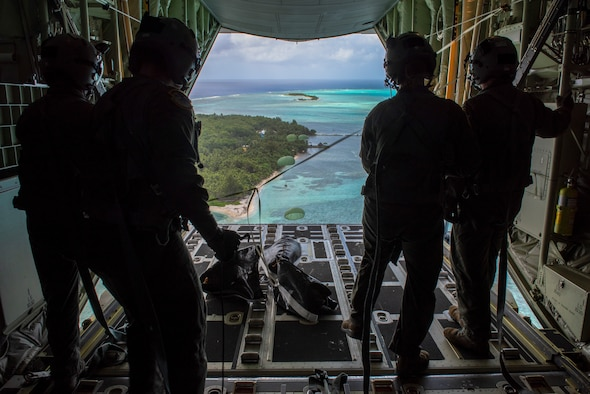 Loadmasters with the 36th Airlift Squadron out of Yokota Air Base, Japan, watch as the four Low-Cost, Low-Altitude humanitarian assistance bundles they just airdropped parachute down to those in need during Operation Christmas Drop 2019, at Nomwin, Federated States of Micronesia, Dec. 13, 2019.