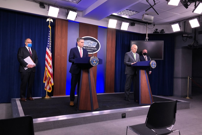 Men stand at lecterns in the Pentagon briefing room.