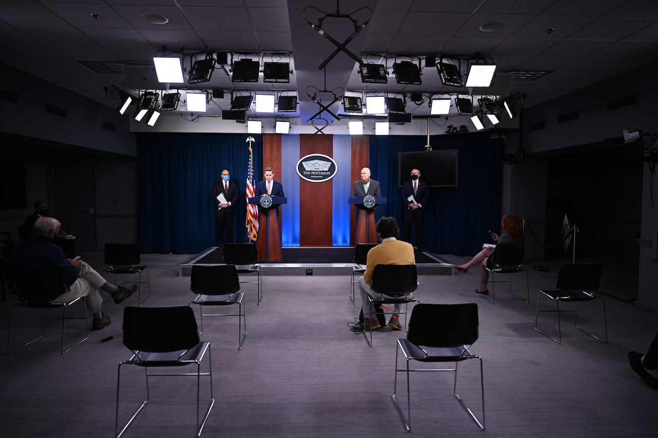 Men stand behind lecterns in a briefing room.