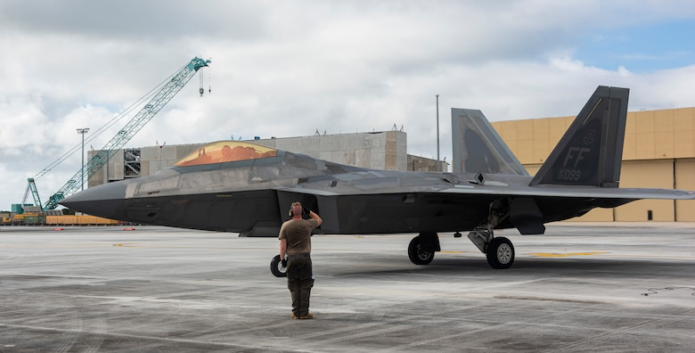 U.S. Air Force Staff Sgt. Jacob Bonter, a dedicated crew chief assigned to the 94th Fighter Squadron, salutes to an F-22 assigned to the 94th FS as it taxies off after completing a hot refuel during a Dynamic Force Employment at Andersen Air Force Base, Guam, Nov. 22, 2020. DFE is an operational platform that allows our forces to be strategically predictable and operationally unpredictable. The United States security presence, along with our allies and partners, underpins the peace and stability that has enabled the Indo-Pacific region to develop and prosper for more than seven decades. (U.S. Air Force photo by Senior Airman Michael S. Murphy)