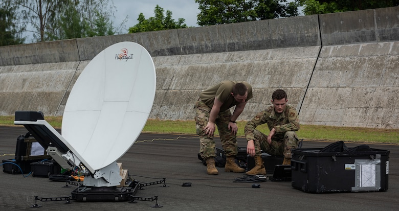 U.S. Air Force Staff Sgt. Daniel Steuer (left), a system supervisor assigned to the 374th Communications Squadron, Yokota Air Base, Japan, and USAF Airman 1st Class Kinsley Noel, a 374th CS radio frequency technician, set up a Hawkeye satellite at Babelthuap, Palau, during a Dynamic Force Employment, Nov. 23, 2020. DFE is an operational platform that allows our forces to be strategically predictable and operationally unpredictable. The U.S.' steadfast commitment to the security and stability of the Indo-Pacific region remains unchanged. (U.S. Air Force photo by Senior Airman Michael S. Murphy)
