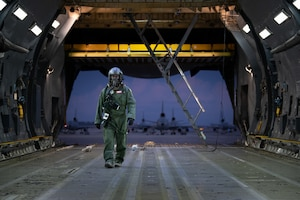 U.S. Air Force Staff Sgt. Cameron DiMatteo, 22nd Airlift Squadron loadmaster, walks inside a C-5M Super Galaxy during a base exercise Nov. 18, 2020, at Travis Air Force Base, California. Airmen at Travis AFB participate in readiness exercises to ensure they can operate in contested environments. (U.S. Air Force photo by Chustine Minoda)