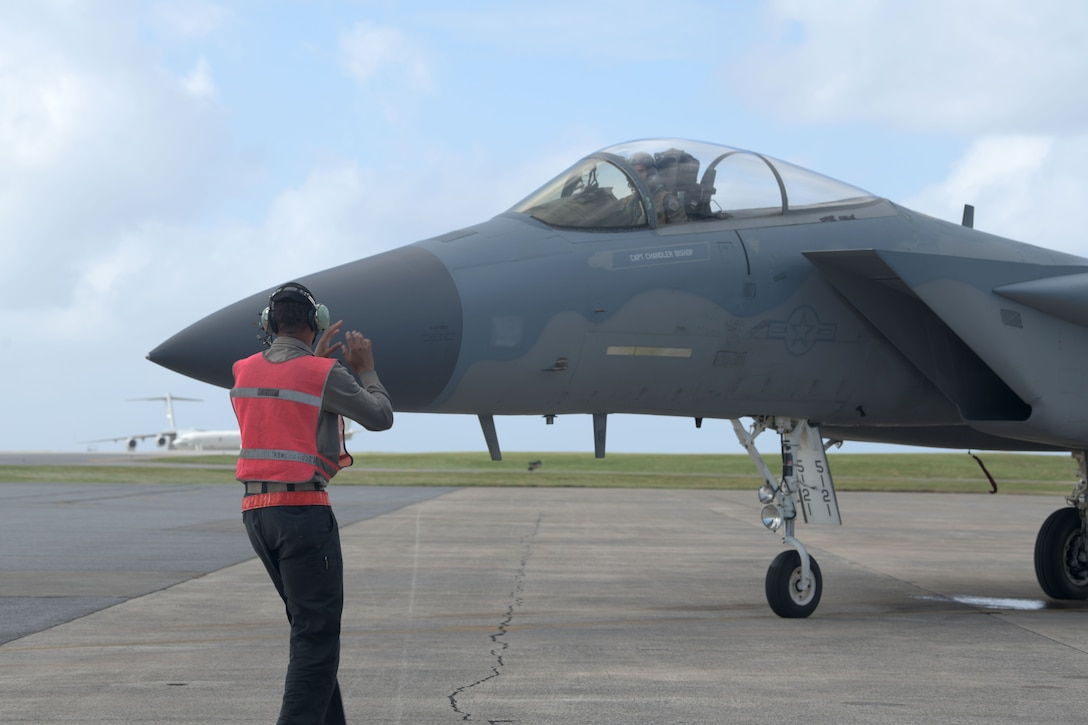 """An F-15C Eagle crew chief leads an F-15C Eagle into a parking space to be refueled by the 18th Logistics Readiness Squadron, during a """"Super Surge,"""" Nov. 18, 2020, at Kadena Air Base, Japan. The 44th and 67th Fighter Squadrons set a new record for the most F-15C Eagles flown in a week at 437 sorties; the previous record was 245 sorties. (U.S. Air Force photo by Airman 1st Class Rebeckah Medeiros)"""