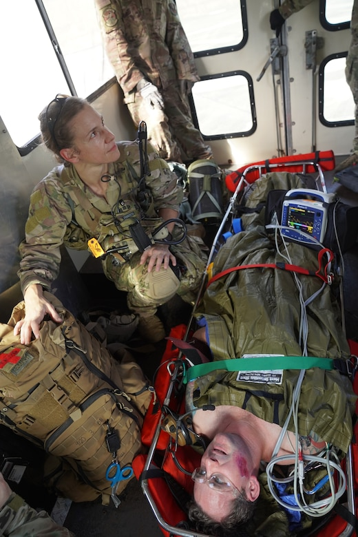 Major Shana Hirchert, 353rd Special Operations Support Squadron flight surgeon, escorts Tech. Sgt. Andrew Bowers, 353 SOSS medical training non-commissioned officer in charge and scenario role-player, ensuring medical care on Kadena Air Base, Japan, after an open water search and rescue training, Nov. 19, 2020.