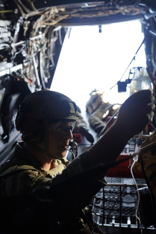 Staff Sgt. Codie White, 353rd Special Operations Support Squadron special operations independent duty medic, prepares a bag of saline fluids in flight ahead of an open water personnel recovery training scenario off the coast of Okinawa, Japan, Nov. 19, 2020.