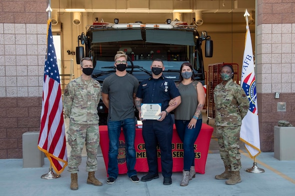 5 adults stand in front of a Fire Truck with the award recipient holding a certificate.