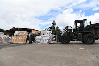 U.S. Air Force Airmen and Members of the Honduran air force unload pallets of humanitarian assistance sent by the Canadian Red Cross to Honduras in response to hurricane Iota at Soto Cano Air Base in Honduras, Nov. 22, 2020.