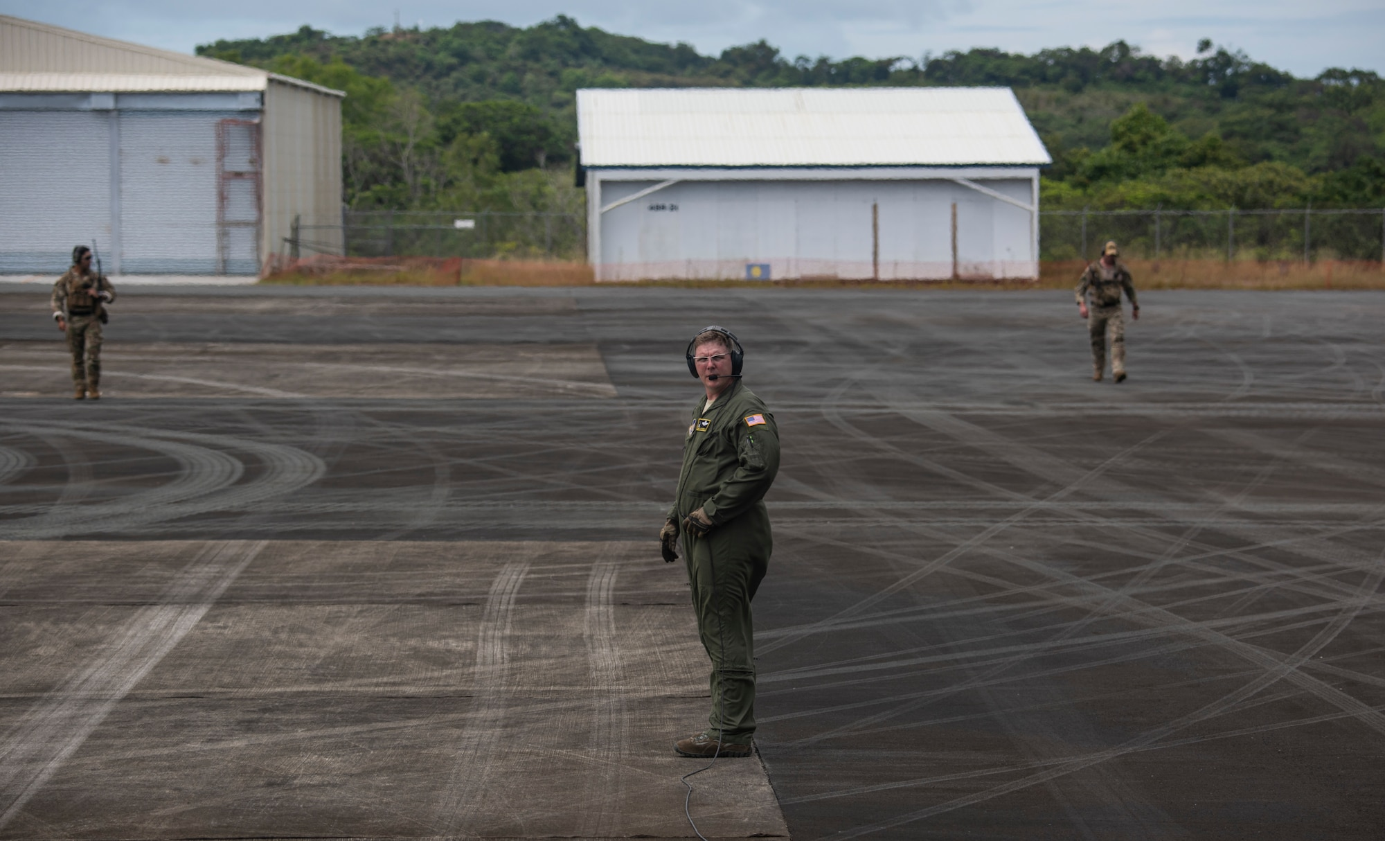 U.S. Chief Master Sgt. Lester Farley, a loadmaster assigned to the 36th Airlift Squadron, Yokota Air Base, Japan, calls in two 736th Security Forces Airmen from a security perimeter before takeoff at Palau International Airport, Palau, during a Dynamic Force Employment, Nov. 23, 2020. DFE is an operational platform that allows our forces to be strategically predictable and operationally unpredictable. The U.S. Air Force is postured and ready to respond to crises and contingencies throughout the U.S. Indo-Pacific Command, contributing to regional stability and a free and open Indo-Pacific. (U.S. Air Force photo by Senior Airman Michael S. Murphy)