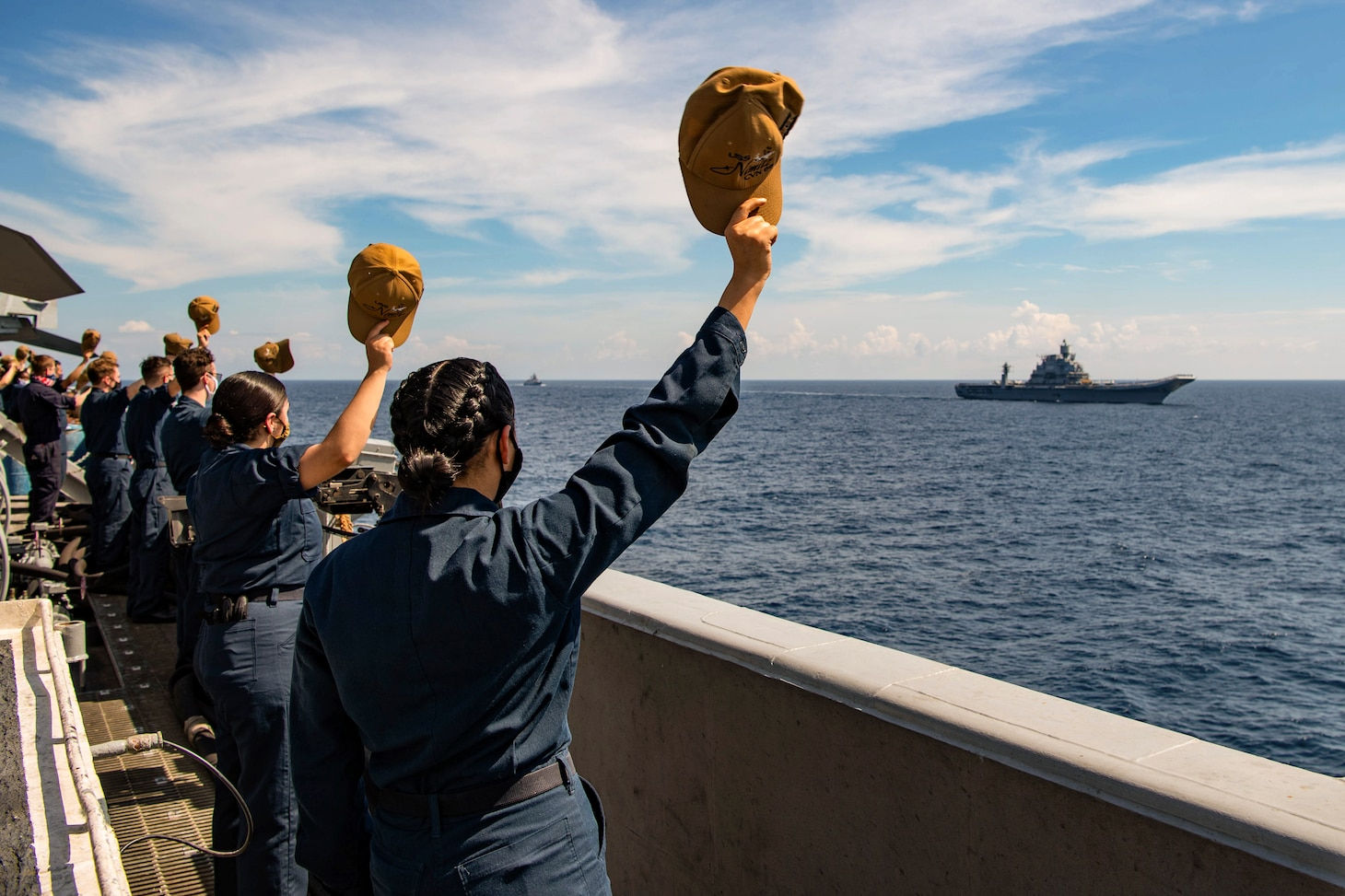Sailors standing on a ship wave their hats at a ship sailing by.