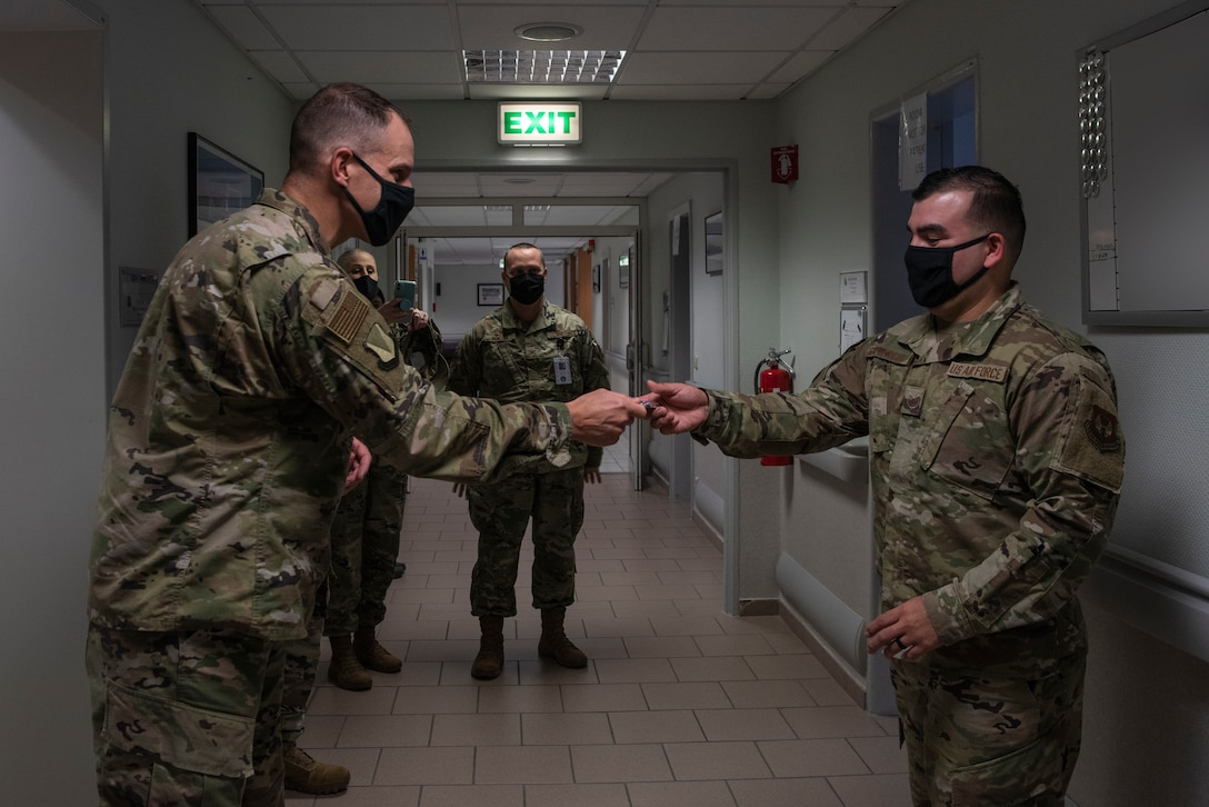 U.S. Air Force Tech. Sgt. Cesar Soto-Betancourt, 86th Dental Squadron general dentistry  noncommissioned officer in charge, receives a coin from Col. Matt Husemann, 86th Airlift Wing vice commander, at Ramstein Air Base, Germany, Nov. 19, 2020.