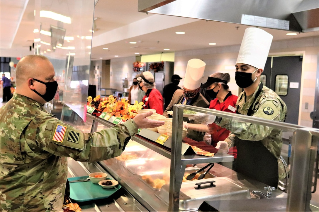 A soldier holds his hand out over a counter for a plate of food.