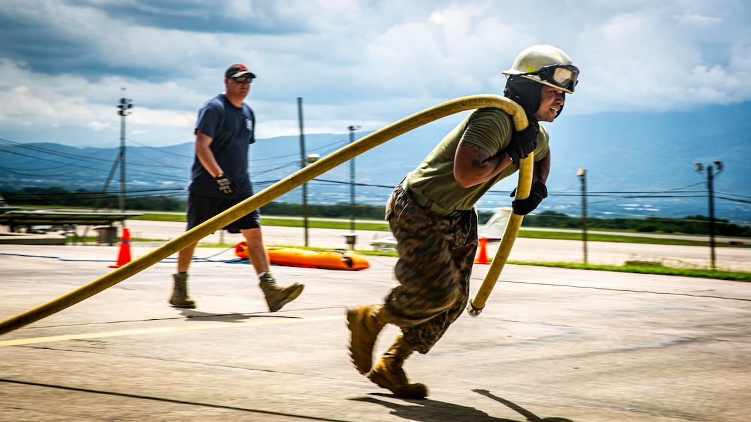 U.S. Marine Corps Master Sgt. Jesus O. Torres, an advisor with Special Purpose Marine Air-Ground Task Force - Southern Command, drags a fire hose during 612th Air Base Squadron's annual fire muster competition at Soto Cano Air Base, Honduras, Oct. 8, 2020. The competition tests a service member's ability to perform basic firefighting techniques and raises awareness of Fire Prevention Week. The U.S. Marines of SPMAGTF-SC continue to perform interagency cooperation with members of Joint Task Force-Bravo to meet mission success and work together to strengthen relationships with partner nations. A group of approximately 20 Marines from the SPMAGTF-SC have joined with JTF-Bravo in Soto Cano Air Base, Honduras, in support of operations and exercises in the Latin American and Caribbean region. Torres is a native of Miami, Florida. (U.S. Marine Corps photo by Lance Cpl. Jose Gonzalez)